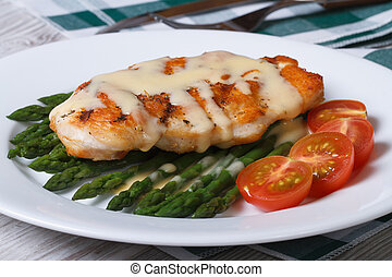 Grilled chicken breast with green asparagus and Hollandaise sauce closeup on white plate. horizontal