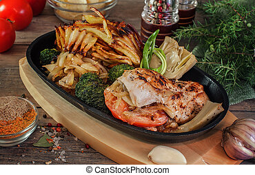chicken breast with onions, artichoke, broccoli, fried potatoes in a frying pan on the village