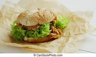Chicken burger lying on parchment - Closeup shot of...