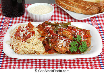 Chicken cacciatore with spaghetti on the side and a side of Italian bread.