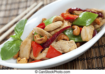 Chicken with cashew nuts, chili, capsicum and snow peas on a bamboo mat with chop sticks