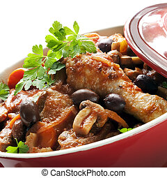 Traditional chicken cacciatore, in a red casserole dish.