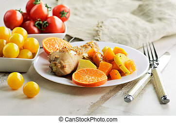 chicken drumstick cooked in spices with vegetables in the plate on the white wooden table. low angle shoot. horizontal