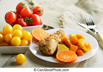 chicken drumstick cooked in spices with vegetables in the plate on the white wooden table. horizontal