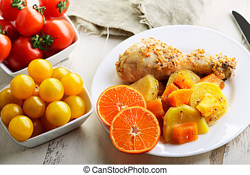 chicken drumstick cooked in spices with vegetables in the plate on the white wooden table. top view. horizontal
