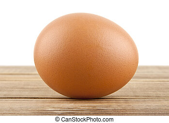 chicken egg on a wooden table isolated on a white background