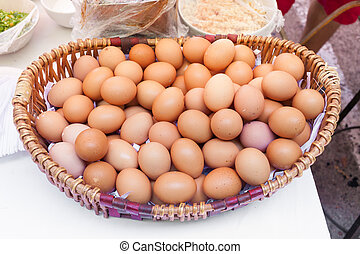 Chicken eggs in a basket isolate on white background