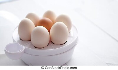 Chicken eggs in a egg electric cooker on a white wooden...