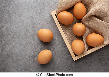 Chicken eggs in the wooden tray on the black cement floor.