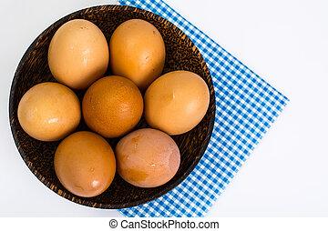 Chicken eggs in wooden bowl on white background