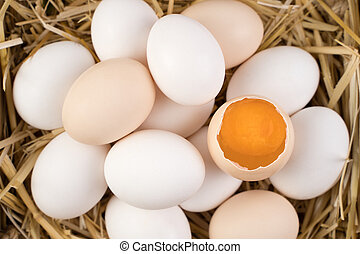 Chicken eggs of white and brown color with a broken egg in the center.