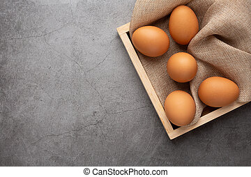 Chicken eggs on the wooden tray on the black cement floor.