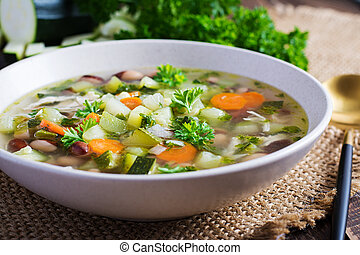 Chicken fillet vegetable soup in  bowl on wooden rustic table.