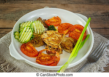chicken fillet with fresh cucumber, artichoke and pepper on white ceramic frying pan