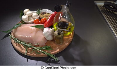 Chicken fillet with vegetables and spices on the table. ...