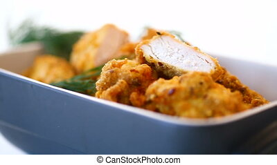 chicken fried in batter with dill in ceramic form on a white background