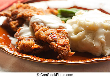 Thin Steak fried and covered in gravy accompanied by mashed potatoes and green beans