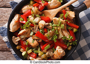 Chicken fried with mushrooms, peppers and zucchini closeup on a pan. horizontal top view