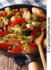 Chicken fried with mushrooms, peppers and zucchini closeup on a pan. vertical