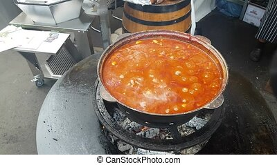 Chicken Goulash In Cauldron - Large cauldron with goulash on...
