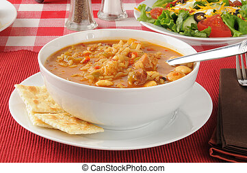 A bowl of chicken sausage gumbo with saltine crackers
