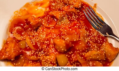 Chicken in sweet and sour sauce with sesame seeds on a plate
