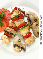 Chicken kebab on a white plate with organic pepper