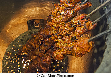 Chicken kebabs cooking in a tandoori oven - Closeup of ...