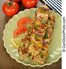 chicken kebabs on a brown background