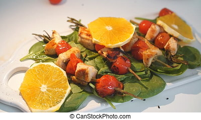 Chicken kebabs served with tomato cherry and greenery on a...