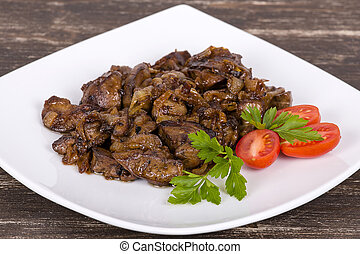 Chicken livers in a creamy sauce with onion on white plate