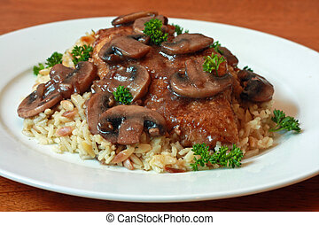 Chicken Marsala served on a bed of rice and orzo.