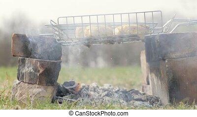 Chicken meat pieces being fried on charcoal grill and fat...