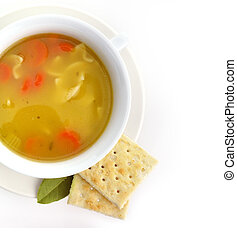 Chicken noodle soup in a white cup with crackers