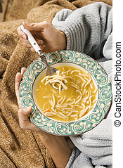 Chicken noodle soup. - Bowl of chicken noodle soup held in...