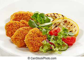 chicken nuggets and vegetables on a white plate