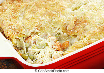 Above view of fresh Chicken Pot Pie with wooden spoon. Section of pot pie removed to reveal chicken, carrots and peas.