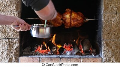 chicken roasting on a spit in garden grill with open fire
