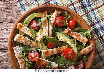 Chicken salad with avocado, arugula and tomatoes closeup. horizontal top view
