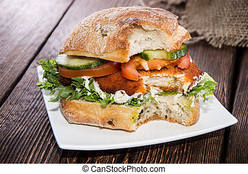 Chicken Sandwich on a plate (wooden background)