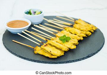 Chicken satay on black slate with sauce