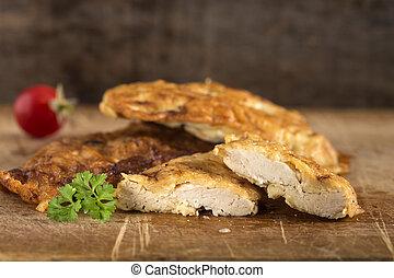 Chicken schnitzel on wood
