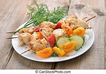Chicken shish kebab on wooden table