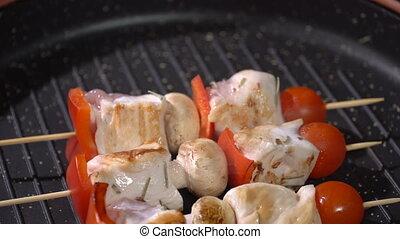 Chicken skewers fried in a pan