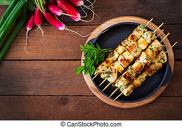 Chicken skewers with slices of apples and chili. Top view