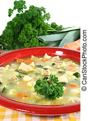 a cup of chicken soup with fresh vegetables