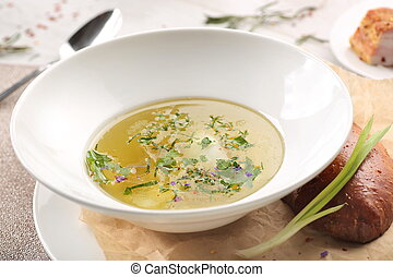 chicken soup with bread in white plate on a white wooden background