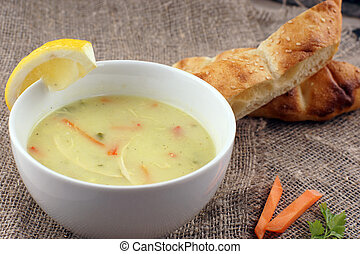 Chicken soup with carrots in a white plate on the table, bread near