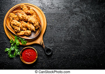 Chicken strips on a plate of greens and sauce in a bowl.