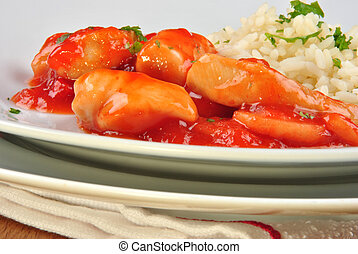 chicken sweet sour with rice on a white plate
